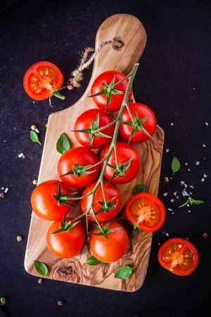 a bunch of fresh organic cherry tomatoes with sea salt and basil on a dark background photo