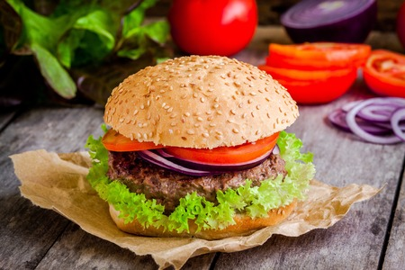 hamburger: homemade hamburger close up with fresh green lettuce, tomato and red onion on rustic background Stock Photo