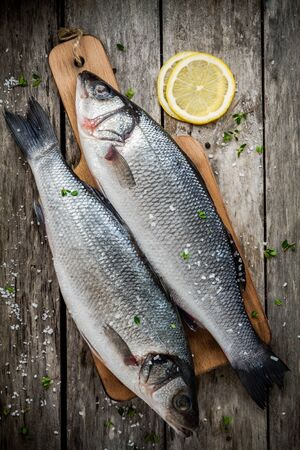 two raw fresh sea bass on a cutting board with lemon and sea salt on wooden rustic table photo
