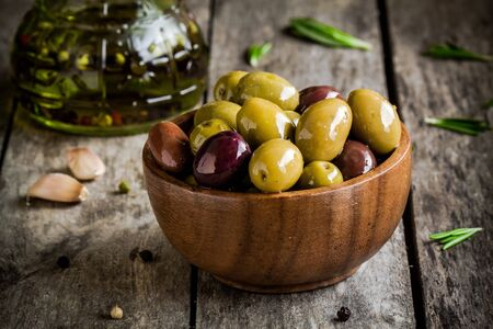 olive green: mixed olives in a wooden bowl with rosemary, olive oil and garlic on rustic table Stock Photo