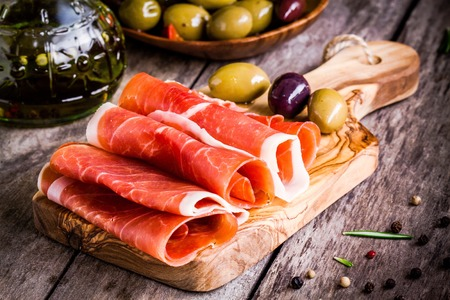 thin slices of prosciutto with mixed olives on wooden cutting board