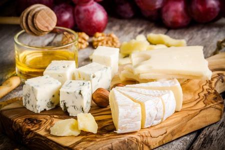 チーズ プレート: エメンタール、カマンベール、パルメザン チーズ、ブルーチーズ、パン棒、クルミ、ヘーゼル ナッツ、蜂蜜、ブドウ 写真素材