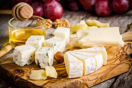queso blanco: Tabla de quesos: Emmental, Camembert, queso parmesano, queso azul, palitos de pan, nueces, avellanas, miel, uvas