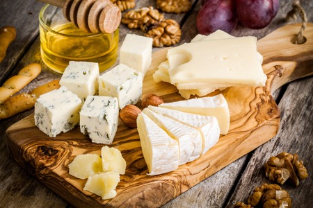 Mix Cheese: Emmental, Camembert, Parmesan, blue cheese, with walnuts and honey on wooden table Reklamní fotografie