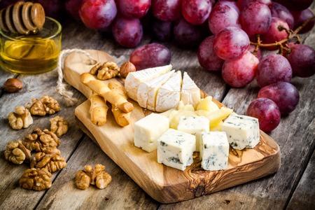 queso: Tabla de quesos: camembert, parmesano, queso azul, palitos de pan, nueces, avellanas, miel, uvas de mesa de madera Foto de archivo