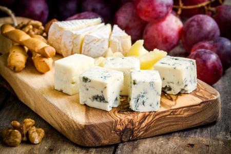 queso: Tabla de quesos: Emmental, Camembert, queso parmesano, queso azul de cerca, con palitos de pan y las uvas de mesa de madera
