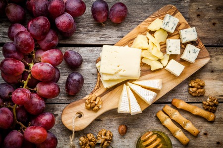 チーズ プレート: エメンタール、カマンベール チーズ、ブルーチーズ、パン棒、クルミ、ヘーゼル ナッツ、蜂蜜、ブドウを木製のテーブルの上