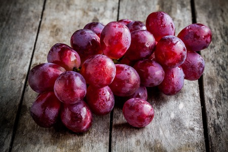 purple red grapes: branch of ripe organic grapes on wooden rustic background Stock Photo