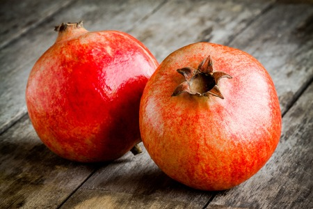 cross cut: two ripe pomegranate on a wooden rustic background