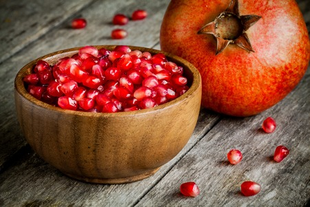 ruby pomegranate grains in a wooden bowl on a rustic table Reklamní fotografie