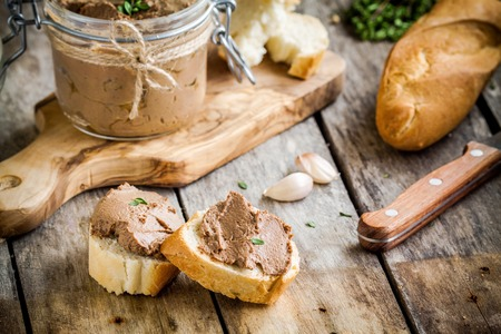sandwiches with homemade chicken liver pate for breakfast on wooden cutting board