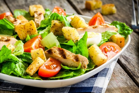 chicken salad: Caesar salad with croutons, quail eggs, cherry tomatoes and grilled chicken on wooden table Stock Photo