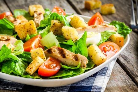 ensalada de tomate: Ensalada César con crutones, huevos de codorniz, tomates cherry y pollo a la parrilla en la mesa de madera