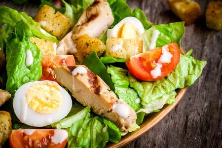 ウズラの卵、チェリー トマト、木製のテーブルのグリルチキンのシーザー サラダ