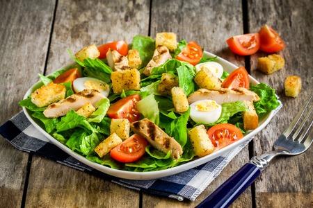 ensalada cesar: Ensalada César con pollo a la parrilla, pan frito, huevos de codorniz y tomates cherry en la mesa de madera rústica