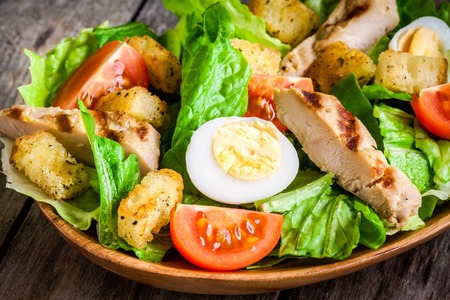 Caesar salad with croutons, quail eggs, cherry tomatoes and grilled chicken on dark background