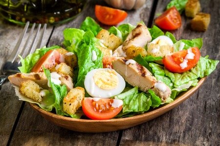 Caesar salad with croutons, quail eggs, cherry tomatoes and grilled chicken in wooden plate on dark rustic table Stockfoto