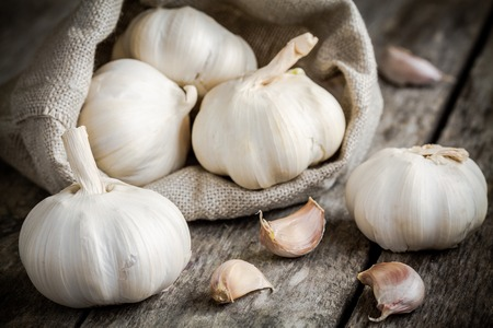 garlic cloves: Organic garlics in the bag on a wooden rustic table