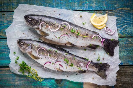 two raw trouts on paper with thyme and lemon and red onion slices on a rustic wooden table