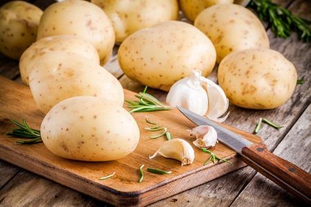 papas: Patatas crudas orgánicas frescas con romero y ajo en una tabla de madera rústica