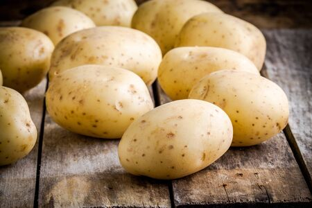 Fresh organic raw potatoes on a wooden rustic table