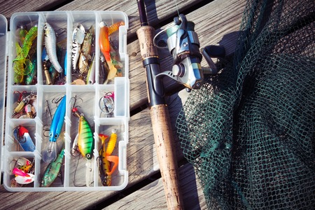 fishermans net: Fishing Lures in tackle boxes with spinning rod and net on wooden pier