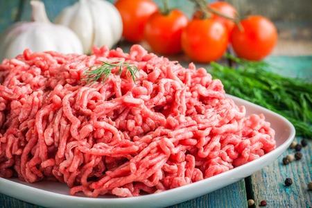 접시에 신선한 원료 다진 쇠고기는 소박한 나무 테이블에 가까이