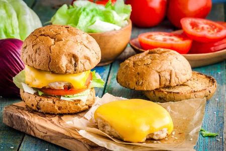 wholegrain mustard: homemade chikenburgers with whole wheat bun, cheddar cheese, fresh tomatoes and lettuce Stock Photo