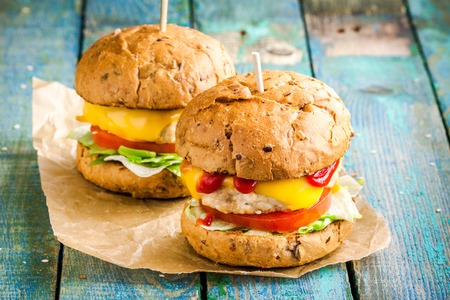 wholegrain mustard: two home burgers with fresh vegetables and chicken cutlets on wooden rustic table