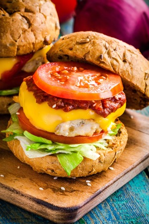 wholegrain mustard: homemade burger with fresh vegetables, barbecue sauce and chicken cutlet closeup Stock Photo