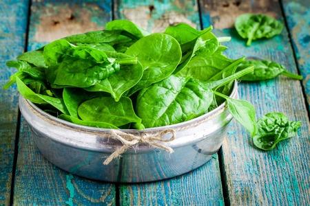 verduras verdes: espinaca orgánica fresca cruda en un tazón en rústica mesa de madera Foto de archivo