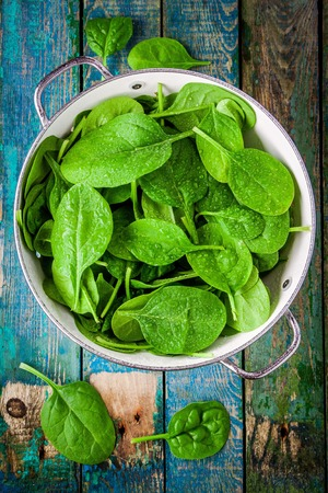 raw fresh spinach with drops in a colander on a rustic wooden table