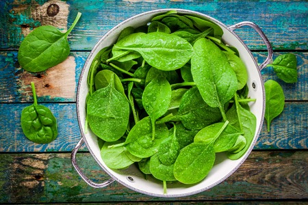 verduras: espinaca fresca cruda con gotas en un colador en una tabla de madera rústica