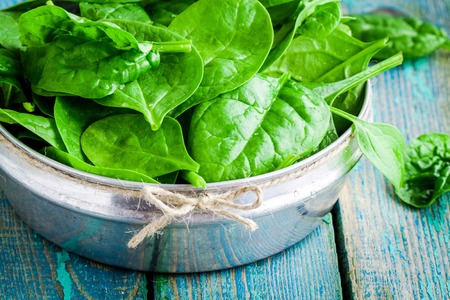 raw fresh organic spinach in a bowl closeup on wooden rustic table photo