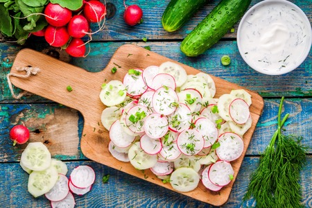 salad of fresh organic radish and cucumber with dill and green onions on cutting board for lunch top view photo