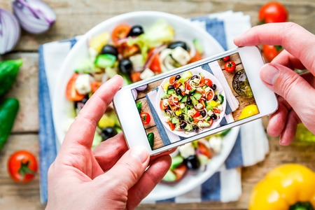 picture: Smartphone taking picture from organic greek salad