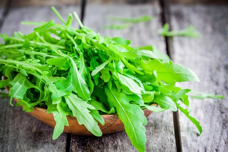 raw vegetables: Fresh organic arugula in a wooden bowl on a rustic table Stock Photo