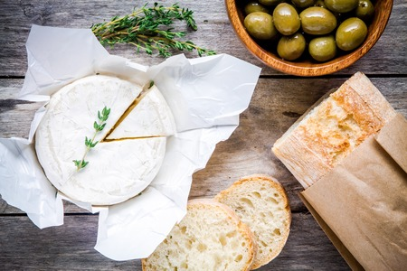 Whole Camembert cheese with thyme, olives and baguette on rustic table