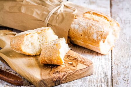French Baguette on cutting board on white rustic table photo