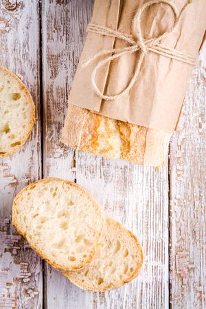 Fresh french Baguette with slices on white rustic table top view photo