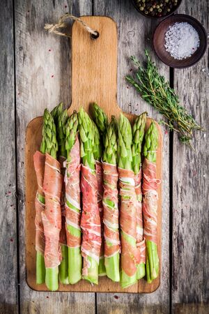 parma ham: Fresh organic asparagus wrapped in Parma ham on a cutting board top view