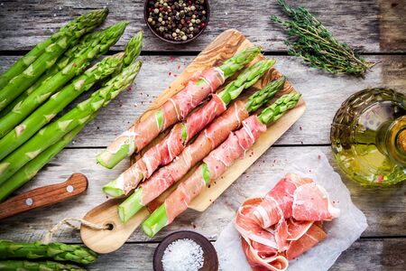 Fresh organic asparagus wrapped in Parma ham on a cutting board top view