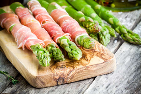parma ham: Fresh organic asparagus wrapped in Parma ham on a cutting board on rustic table