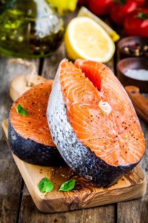 Two fresh raw salmon steaks closeup on wooden cutting board