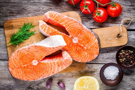 Two fresh raw salmon steaks with salt, peppers, lemon, tomatoes and dill on the rustic table