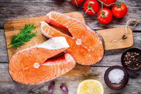Zwei frischen, rohen Lachs Steaks mit Salz, Pfeffer, Zitrone, Tomaten und Dill auf dem rustikalen Tisch Standard-Bild - 40927411