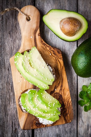 sandwiches with rye bread, sliced avocado, sesame seeds on wooden cutting board photo