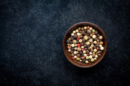 peppar: Peppercorns in a wooden bowl on a dark background