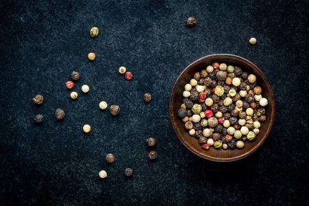 Peppercorns in a wooden bowl on a dark background