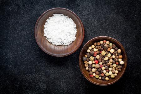 sal: granos de pimienta y sal marina en un cuenco de madera sobre un fondo oscuro Foto de archivo